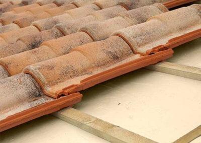 Proceso de cololcación de paneles xps debajo de las tejas claveteadas.